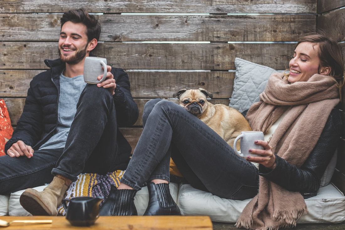 man and woman drinking coffee with pug dog